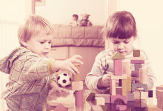 Two tranquil children playing with wooden blocks Royalty Free Stock Image