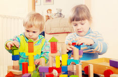 Two tranquil children playing with wooden toys. In home interior stock photos