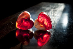 Two translucent red hearts in sun beams. Two translucent red hearts shaped soap in sun beams on dark brown rough background Royalty Free Stock Images