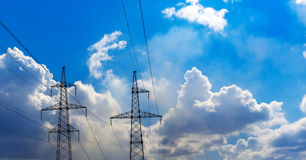 Two transmission towers of a transformer station and a blue sky. Concept for energy and technology. Royalty Free Stock Images