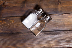 Two transparent cans of salt and pepper shaker on wooden background Stock Photos