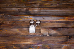 Two transparent cans of salt and pepper shaker on wooden background Royalty Free Stock Image