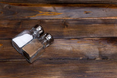 Two transparent cans of salt and pepper shaker on wooden background Stock Image