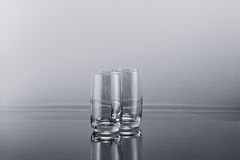 Two transparent empty tall glasses. On a gradient simple background Royalty Free Stock Image
