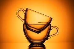 Two transparent glass mugs for tea. Orange background, close-up, HORIZONTAL LAYOUT stock image
