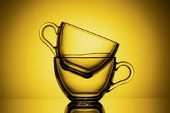 Two transparent glass mugs for tea. Yellow background, close-up, HORIZONTAL LAYOUT royalty free stock photography