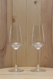 Two transparent glass standing with a wooden background Royalty Free Stock Photos