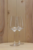 Two transparent glass standing on a wooden stand with a wooden background Royalty Free Stock Photos