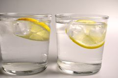 Two transparent glasses with colorless liquid - water, alcohol. On white background stock photos