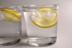 Two transparent glasses with colorless liquid - water, alcohol. On white background stock image