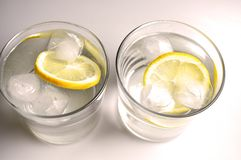 Two transparent glasses with colorless liquid - water, alcohol. On white background royalty free stock images