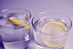 Two transparent glasses with colorless liquid - water, alcohol. On white background royalty free stock image