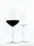 Two transparent glasses - one full of red wine and the other is empty - on a white background Royalty Free Stock Images