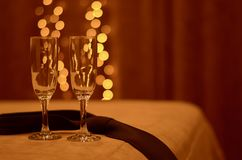 Two romantic glasses on the edge of the bed in the light of warm lights, next to a man`s tie. royalty free stock photo