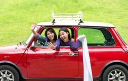 Two travel woman in car road trip waving Stock Photos