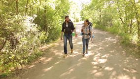 Two travelers with backpacks walk in the woods. Two travelers with large backpacks on their back walk along the road in the forest in the summer. Active rest in stock video footage