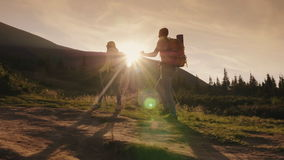 Two travelers climbs a mountain. Silhouettes in the rays of the setting sun. stock footage