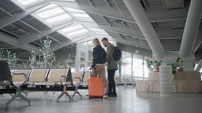 Man and woman are walking through waiting hall of station, back view. Two travelers are going over hall of terminal, rolling their suitcases, back view. They are stock video footage