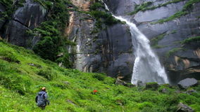 Two travelers greet each other at the Jogini waterfall in Vishesht, near Manali, India stock video footage