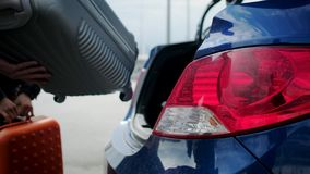 People are putting suitcases into trunk of automobile, close-up view. Two travelers are loading baggage inside trunk of car, detail view. Automatically open door stock footage
