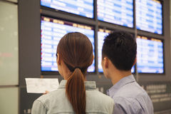 Two travelers looking at flight departure screens at airport Royalty Free Stock Photos
