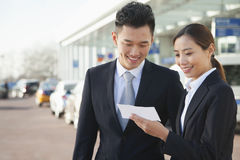 Two travelers looking at ticket in airport Stock Photo
