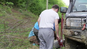 Two travelers replacing wheel of expeditionaty SUV at forest dirty road. Two caucasian travelers replacing wheel of expeditionaty SUV at forest dirty road stock video