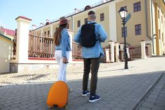 Two travelers on vacation walking around the city with luggage. Stock Photos