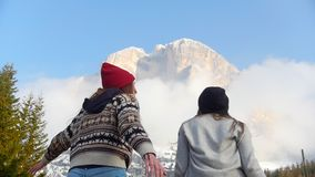 Two traveling happy young women jumping in front of the mountain stock footage