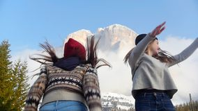 Two traveling happy young women running towards the mountain and jumping stock video