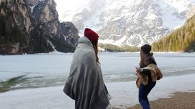 Two traveling young women covered in the blankets walking to the frozen lake stock footage