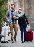 Two travellers with digital camera walking through city street Stock Photos