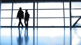 Two travellers going in airport in front of window opposite the runway, silhouette. Wide angle stock footage