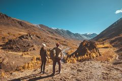 Two travellers looks at mountains and valley stock photos