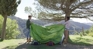 Two travellers putting up tent stock video
