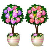 Two trees with leaves and red and pink spotted Easter eggs in stylized shell pots. Symbol and decoration for holiday Royalty Free Stock Photo