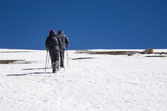 Two trekkers going to the top of snow-covered slope. Stock Photo