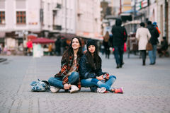 Two trendy and fashionable street girls skateboarders joking and smiling. Girls dressed in stylish clothes Stock Images