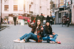 Two trendy and fashionable street girls skateboarders joking and smiling Royalty Free Stock Images