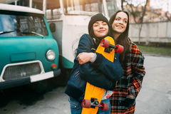 Two trendy and fashionable street girls skateboarders joking and smiling Stock Image