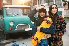 Two trendy and fashionable street girls skateboarders joking and smiling Stock Images