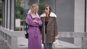 Two trendy and fashionable women are wearing coats are standing on city street and talking to each other stock footage