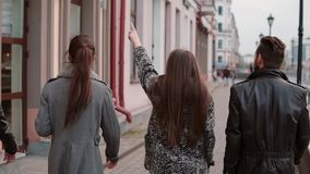 Two trendy girls and two stylish men cheerfully walk in the city and talk. Slow mo, steadicam shot, back view. Three brunette and one red-haired people walk in stock video footage