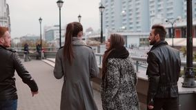 Two trendy girls and two stylish men cheerfully walk in the city and talk. Slow mo, steadicam shot, back view stock video footage