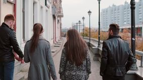 Two trendy girls and two stylish men walk in the city. Buildings at the background. Slow mo, steadicam shot, back view. Two trendy girls and two stylish men stock video