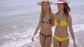 Two trendy young woman strolling along a beach stock video footage