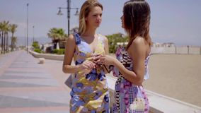 Two trendy young women having a serious talk. Two trendy young women in colorful summer dresses having a serious talk on a seafront promenade with focus to an stock video
