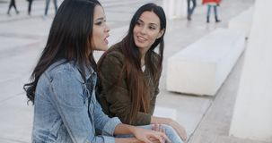 Two trendy young women relaxing. On a white bench on a city promenade chatting  panoramic view with copyspace stock video