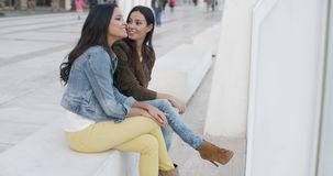 Two trendy young women relaxing. On a white bench on a city promenade chatting  panoramic view with copyspace stock footage