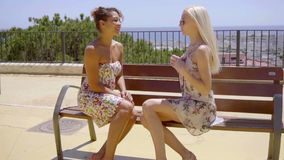 Two trendy young women sitting chatting. Together on a bench in the summer sunshine on a promenade overlooking a city stock footage